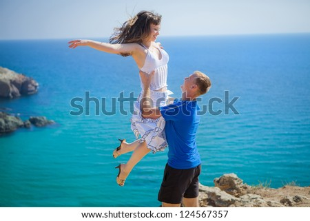 Young loving couple jumping and having fun on the beach, enjoying their summer holiday together. Honeymoon. - stock photo