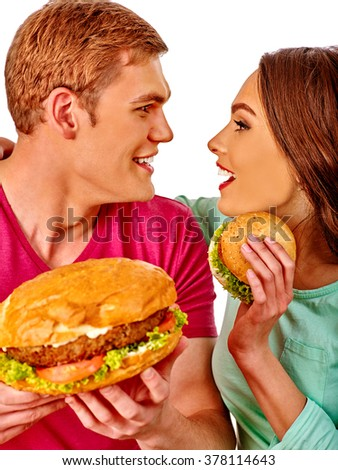 Young loving couple man and woman look in eye each other and eating hamburgers  . Fastfood concept.  Isolated. - stock photo