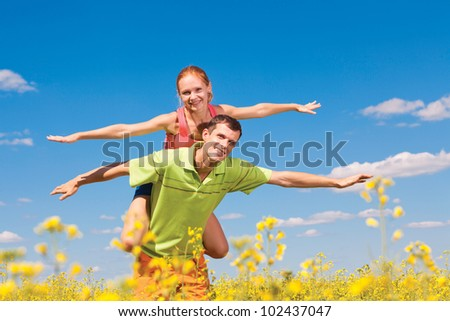 Young loving couple on a green field - stock photo