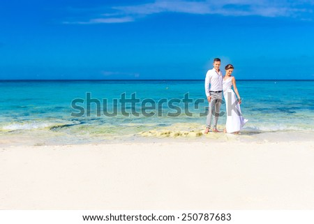 young loving couple on their wedding day, outdoor beach wedding in tropics - stock photo