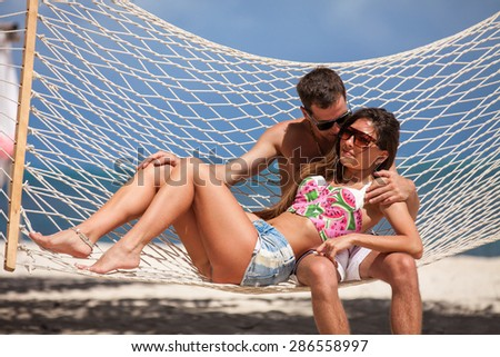 young loving couple on their wedding day, relaxing in beach hammock, outdoor beach wedding in tropics - stock photo