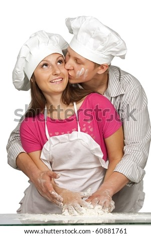 Young loving couple playing with dough. Over white background - stock photo