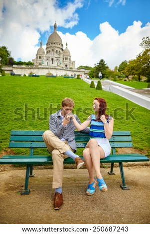 Young loving couple sitting on a bench near the Sacre-Coeur in Paris - stock photo