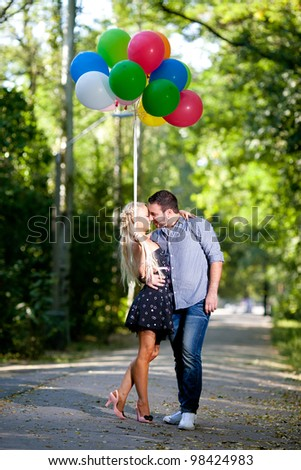 young loving couple with balloons on natural background - stock photo