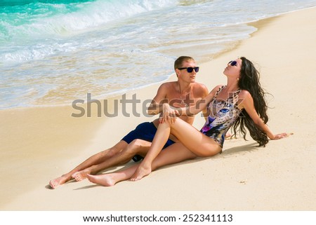 young loving happy  couple on tropical beach, sitting on sand - stock photo