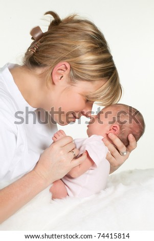 Young loving mother hugging her sleeping 18 days old baby - stock photo