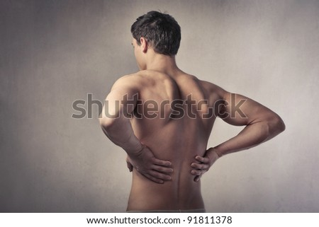 Young ma suffering from backache - stock photo