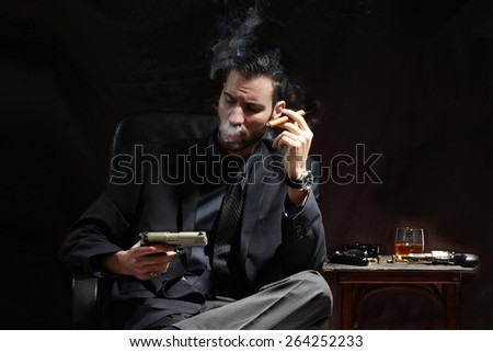Young mafia man hold gun and smoke cigar on dark background - stock photo
