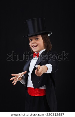 Young magician boy using his magic wand and smiling - on black background - stock photo