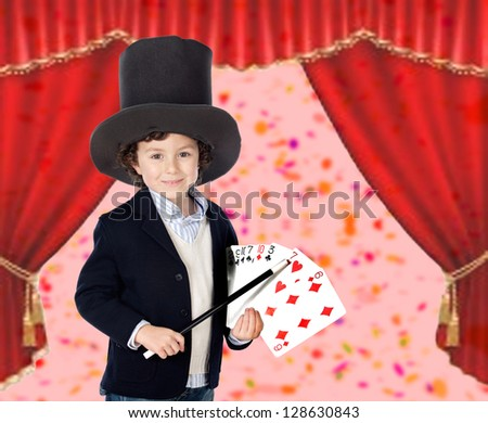 Young magician doing a card trick in a theater - stock photo