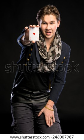 Young magician showing ace on a black backgrouns - stock photo