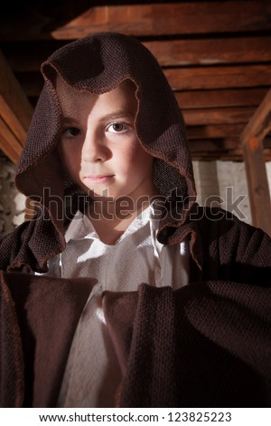 Young magician with folded arms hidden in his cloak - stock photo