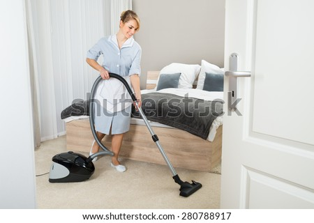 Young Maid Cleaning In Hotel Room With Vacuum Cleaner - stock photo