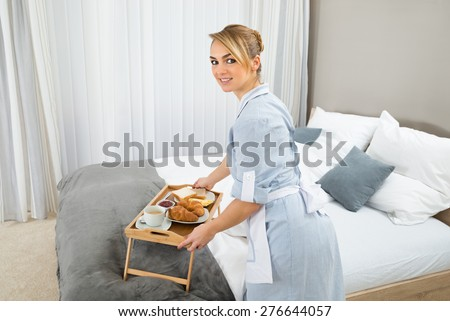 Young Maid Keeping Breakfast Tray In Hotel Room - stock photo