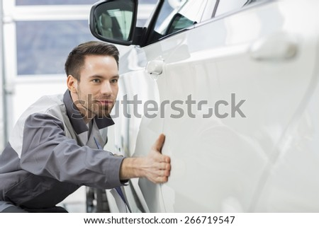 Young maintenance engineer examining car in repair shop - stock photo