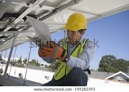 Young maintenance worker looking at clipboard under solar panels - stock photo