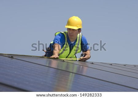 Young maintenance worker measuring solar panels on rooftop - stock photo