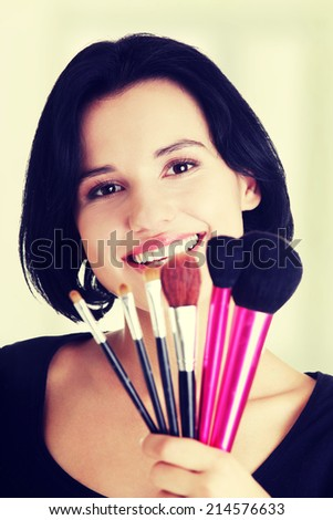 Young make-up artist woman holding brushes , isolated on white - stock photo