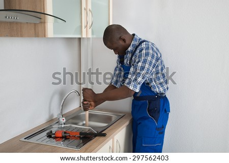 Young Male African Plumber Pressing Plunger In Kitchen Sink - stock photo