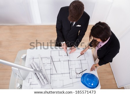 Young male and female architects discussing over blueprint at desk in office - stock photo
