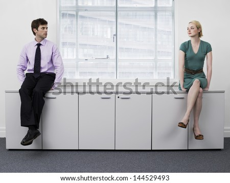 Young male and female business people sitting on office cabinets - stock photo