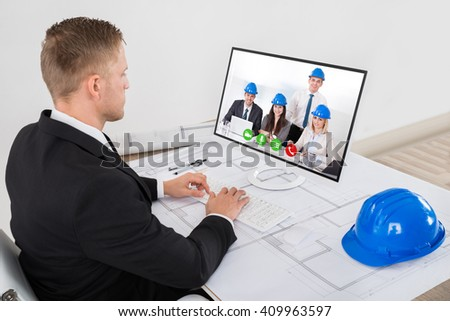 Young Male Architect Attending Video Conference On His Computer In Office - stock photo