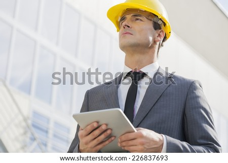 Young male architect holding tablet PC against building - stock photo