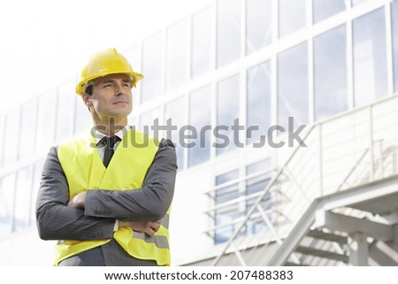 Young male architect in protective wear standing arms crossed outside building - stock photo