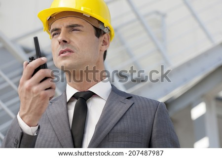 Young male architect talking on two-way radio outdoors - stock photo