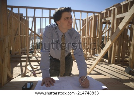 Young male architect working on blueprint at construction site - stock photo