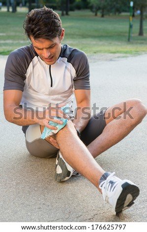 Young Male Athlete Sitting On Ground And Taking Ice For Knee Pain  - stock photo