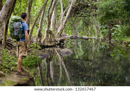 Young male backpacker enjoys view of jungle river. - stock photo