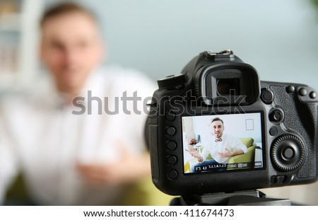 Young male blogger recording video at home - stock photo