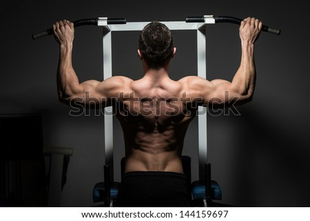 young male bodybuilder doing heavy weight exercise - stock photo