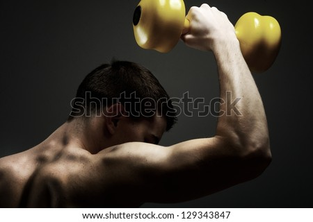Young male bodybuilder doing heavy weight exercise with dumbbells against dark background - stock photo