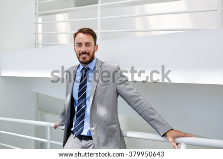 Young male boss smiling for camera while resting after successful meeting with international partner, cheerful man skilled entrepreneur dressed in luxury suit standing in hallway of his big company - stock photo