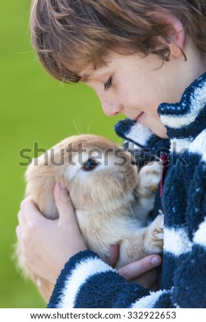 Young male boy child outside playing with his pet rabbit - stock photo
