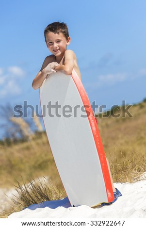 Young male boy child with white surfboard or boogie board on a beach with bright blue sky - stock photo
