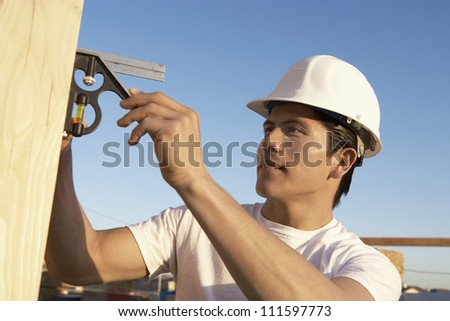 Young male carpenter with spirit level working at construction site - stock photo