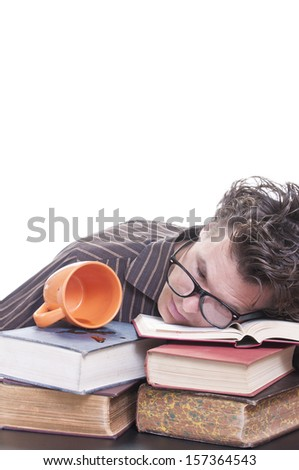 Young male Caucasian student falls asleep on books next to spilled cup of coffee on white background with copy text space - stock photo