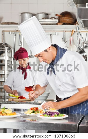 Young male chef garnishing dish with female colleague in background - stock photo