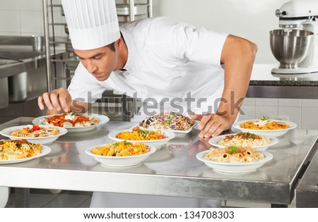 Young male chef garnishing dishes at commercial kitchen counter - stock photo