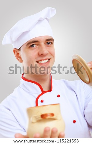 Young male chef in red apron against grey background - stock photo