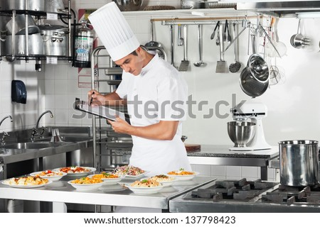 Young male chef with clipboard going through cooking checklist at commercial kitchen counter - stock photo