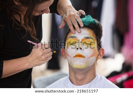 Young male clown getting makeup on face - stock photo