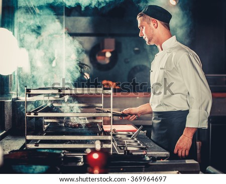 Young male cook preparing meal on the grill in kitchen - stock photo