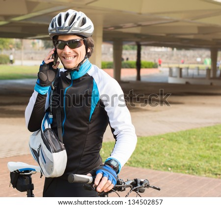 Young Male Cyclist Talking On Cell Phone; Outdoors - stock photo