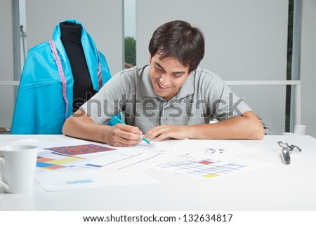 Young male designer drafting new designs on paper at workshop - stock photo