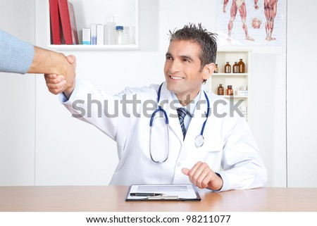 Young male doctor and patient shake hands at clinic. - stock photo