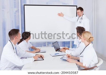 Young male doctor giving presentation to colleagues in conference room - stock photo